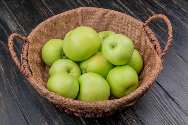 Вид сбоку зеленых яблок в корзине на деревянном