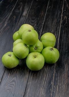 Вид сбоку зеленых яблок на деревянном фоне