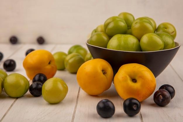 Вид сбоку зеленой алычи на миске с фруктами, такими как персики, изолированные на деревянном фоне