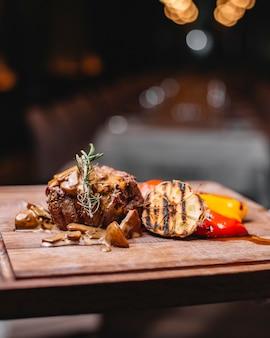 Вид сбоку жареной говядины с грибами на гриле с овощами и соусом на деревянной доске