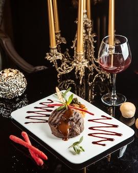 테이블에 하얀 접시에 소스와 야채와 구운 쇠고기 메달의 측면보기