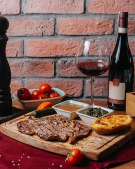 Вид сбоку на гриле стейк из говядины с печеным картофелем и соусом на деревянной доске
