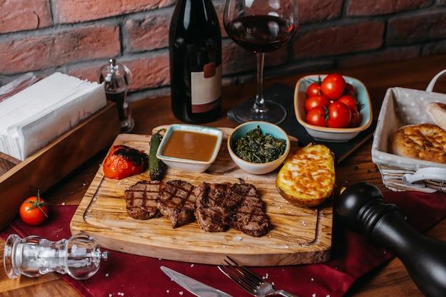 나무 보드에 구운 potatoe 야채와 소스와 구운 쇠고기 스테이크의 측면보기