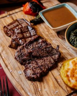 나무 보드에 소스와 구운 쇠고기 스테이크의 측면보기