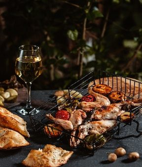 Вид сбоку жареной курицы с овощами и бокал вина на черном столе