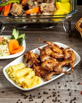 Вид сбоку перепелиного гриля с люля-кебабом из картофеля, подается с овощным салатом на столе