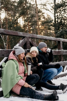 冬に屋外で飲み物を飲んでいる友人のグループの側面図