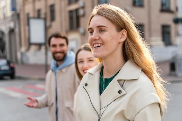 도시에서 야외에서 웃는 친구의 그룹의 측면보기