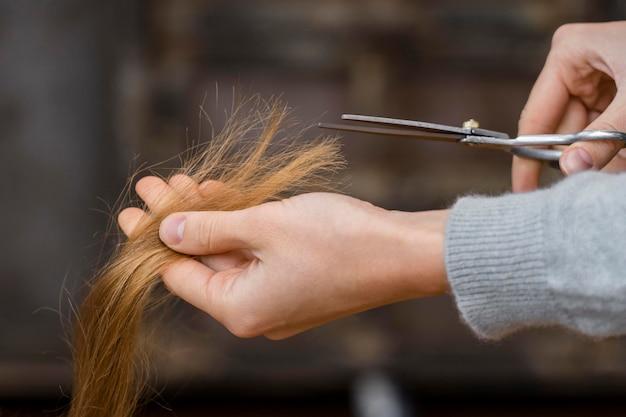 Парикмахер стрижет волосы, вид сбоку