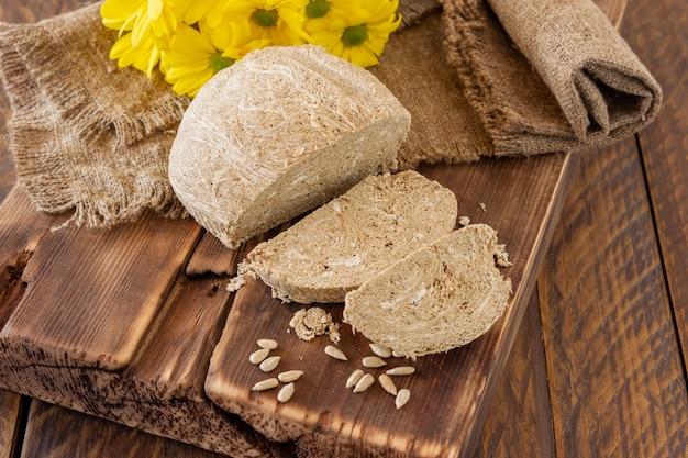땅콩 기름진 씨앗을 페이스트로 갈아서 설탕 시럽과 섞어 만든 동양식 달콤한 디저트인 할바의 측면은 꽃과 함께 나무 책상에 제공됩니다.
