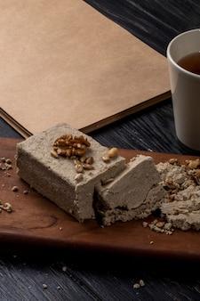 Вид сбоку халвы с семечками и грецкими орехами на деревянной доске и чашка чая на деревенском