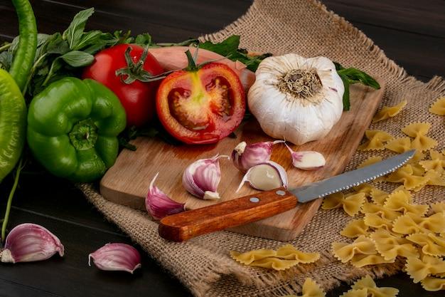 Вид сбоку половинки помидора с ножом и чесноком на разделочной доске с пучком мяты и сырых спагетти на бежевой салфетке