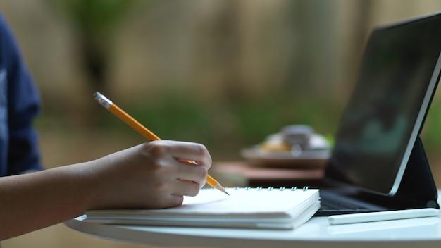 自宅の庭でオンライン勉強しながら空白のノートに書くために鉛筆を持っている手の側面図