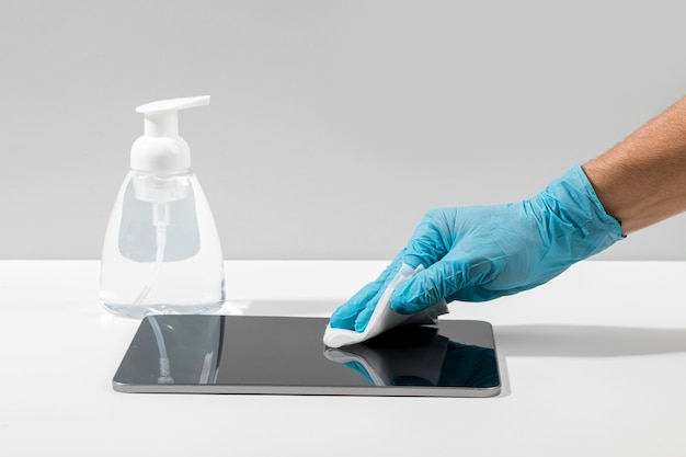Взгляд со стороны руки с таблеткой хирургической перчатки дезинфицируя на столе