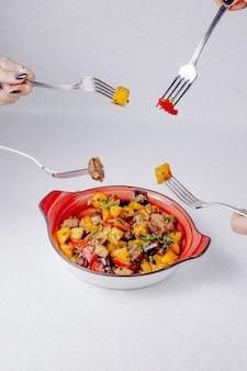 Вид сбоку руки держат вилки над миской с тушеным мясом, картофелем и овощами