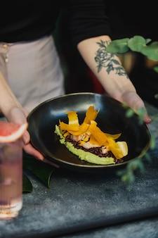 Вид сбоку руки держат черную тарелку с зеленым шпинатом перегной с коричневым рисом и креветками