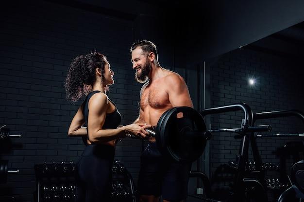 잘 생긴 수염 난 남자와 미소하고 어두운 체육관에서 바벨로 운동하는 동안 서로를보고 아름다운 여자의 측면보기