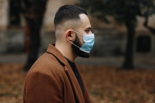 의료 얼굴 마스크에 거리에 서있는 베이지 색 코트를 입은 잘 생긴 수염 난된 남자의 측면보기. 예방 및 코로나 바이러스.