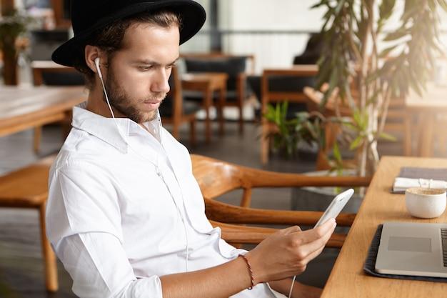 Взгляд со стороны красивого бородатого человека в черной шляпе и белых наушниках звоня видео- к его партнеру используя мобильный телефон. кавказский студент слушает музыку, ждет своего друга в кафе