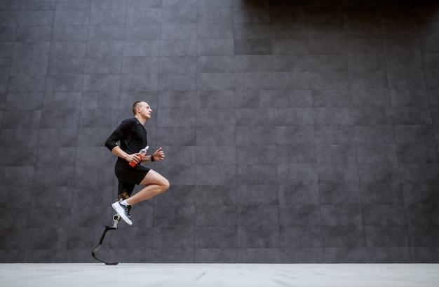 外で実行されている義足でハンサムなフィット白人スポーツマンの側面図です。