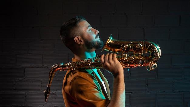 Красивый мужчина-музыкант, держащий саксофон, вид сбоку