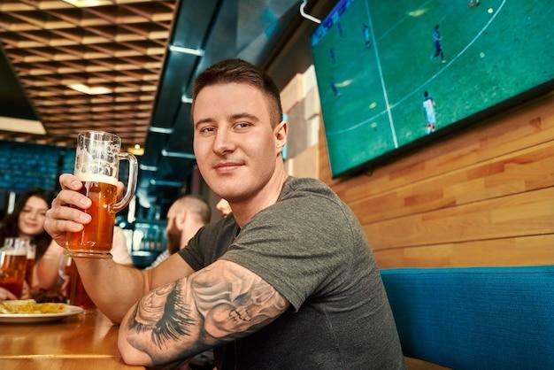 맥주를 마시고, 카메라를보고, 바에서 웃고있는 문신 잘 생긴 남자의 측면보기. 주말에 술집에서 친구와 함께 쉬고있는 동안 포즈를 취하는 젊은 남성. 여가와 재미의 개념.