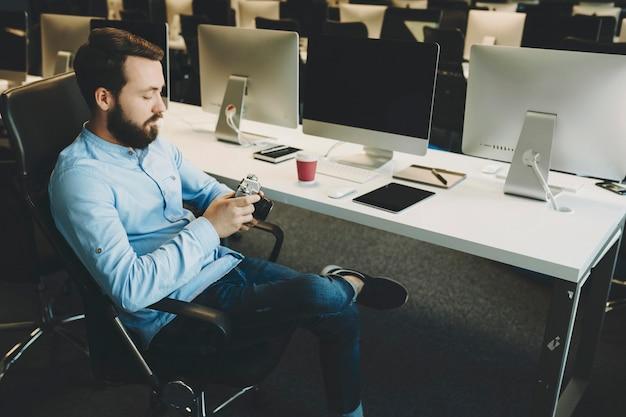 사무실에서 작업하는 동안 의자에 앉아 카메라에 사진을보고 잘 생긴 젊은 남자의 측면보기