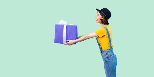 힙스터를 입은 행복한 아름다운 소녀의 옆모습은 데님 작업복을 입고 검은 모자를 쓰고 이빨 미소가 있는 크고 무거운 선물 상자를 줍니다. 스튜디오 촬영, 녹색 배경, 절연