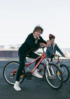 그들의 자전거와 함께 도시에서 야외에서 행복한 소년의 측면보기