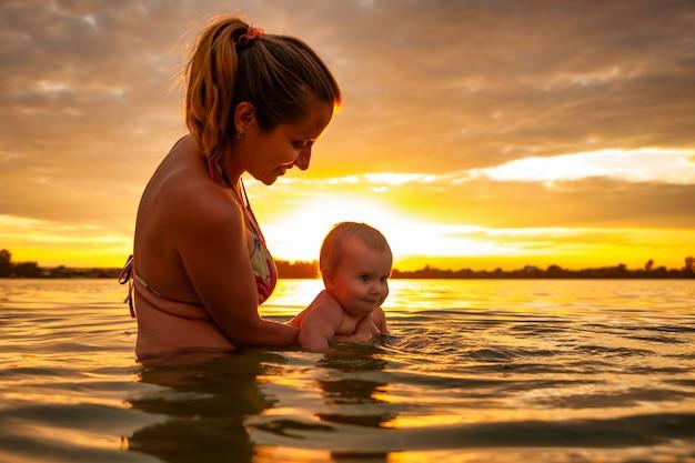 Вид сбоку счастливой кавказской матери, обучающей плаванию маленького милого улыбающегося ребенка в морской воде