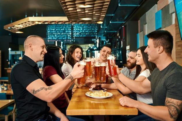 큰 테이블에 앉아서 술집에서 맥주를 즐기는 행복한 회사의 측면보기. 맥주를 마시고, 토스트하고 카페에서 함께 웃고 쾌활한 동료. 행복과 재미의 개념.