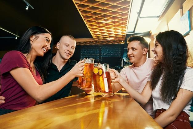 술집에 함께 앉아 주말에 맥주를 마시는 행복한 회사의 측면보기. 쾌활한 젊은 남성과 여성이 서로를보고, 이야기하고 웃고 바에서. 재미와 행복의 개념.