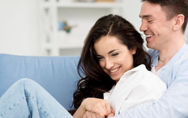 自宅のソファーに幸せなカップルの側面図