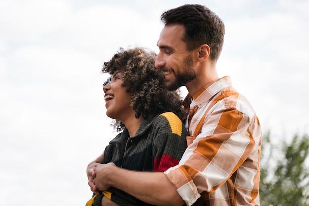 Вид сбоку счастливой пары, проводящей время вместе на открытом воздухе