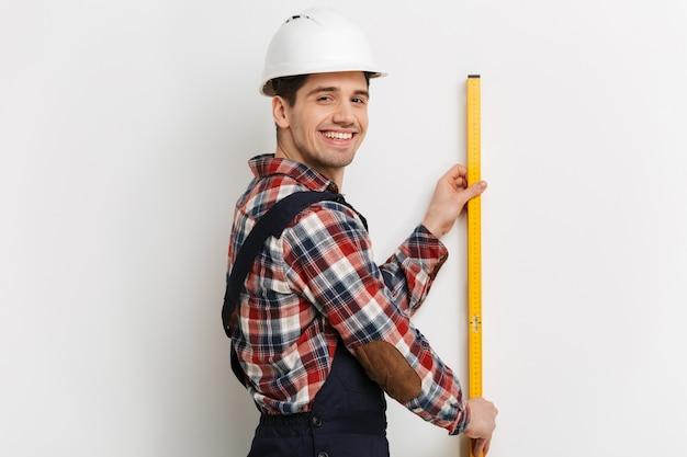 灰色の壁の上の壁にレベルツールを保持している保護用のヘルメットで幸せな男性ビルダーの側面図