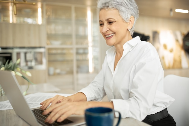 Вид сбоку счастливой деловой женщины средних лет с короткими седыми волосами, работающей на ноутбуке в ее стильном офисе с руками на клавиатуре, печатая письмо и делясь хорошими новостями