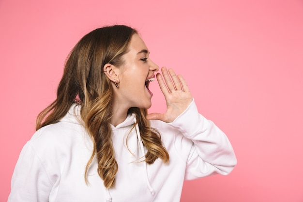 분홍색 벽 너머를 바라보며 평상복을 입고 비명을 지르는 행복한 금발 여성의 측면