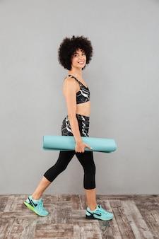 フィットネスマットと歩いてハッピースポーツ女性の側面図