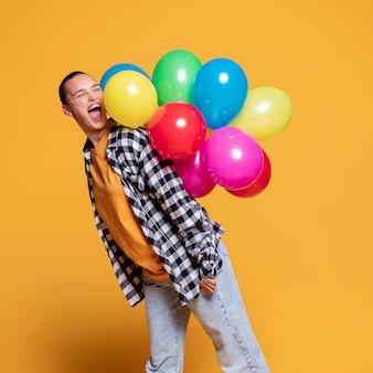 Вид сбоку счастливая женщина с красочными воздушными шарами