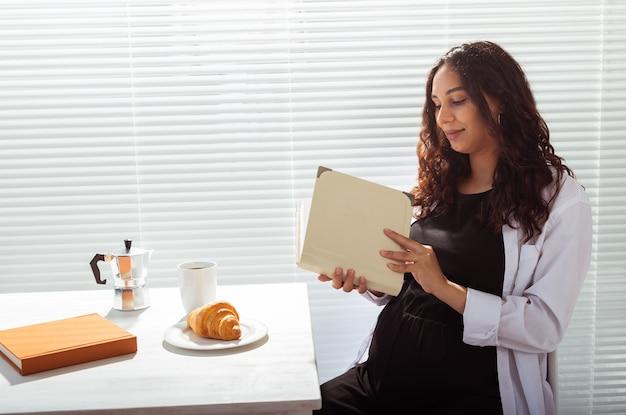 ブラインドの壁にコーヒーとクロワッサンと朝の朝食をしながら本を読んで幸せな若い美しい女性の側面図。おはようコンセプトと楽しい昼休み