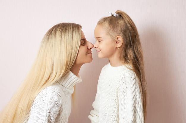 長いブロンドの髪を持つ幸せな若い女性がお互いに押し付けられた鼻の先端でポーズをとっている彼女の魅力的な小さな娘にキスしようとしている側面図。愛、家族、世代、関係