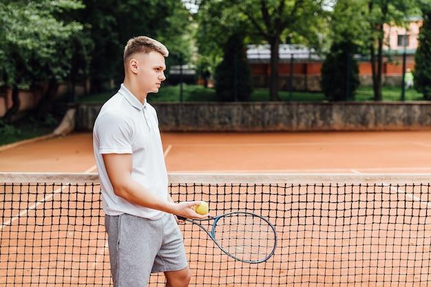 폴로 셔츠를 입은 행복한 청년의 측면은 테니스 라켓을 손에 들고 테니스 코트에 서 있는 동안 웃고 있습니다.