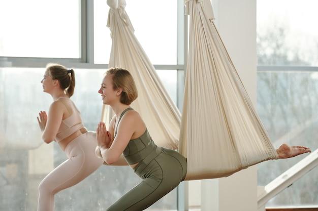 Вид сбоку счастливых молодых спортсменок в спортивных костюмах, использующих оборудование для йоги во время упражнений с руками, сложенными на груди