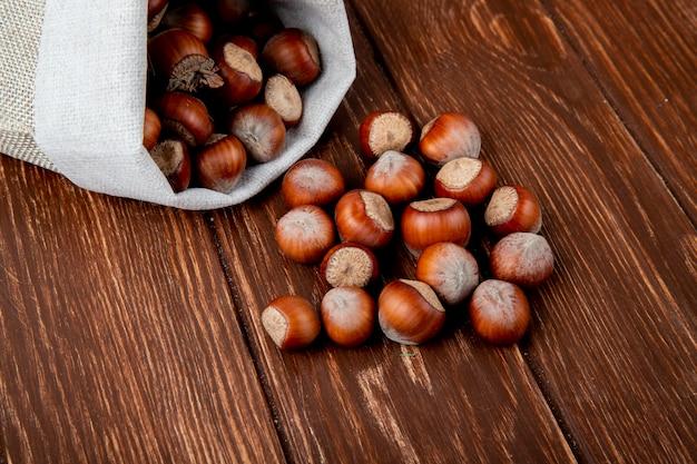 木製の背景に袋から散乱シェルのヘーゼルナッツの側面図