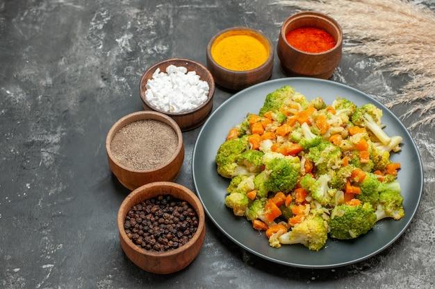 黒いプレートにブロッコリーとニンジン、灰色のテーブルにスパイスを使った健康的な食事の側面図