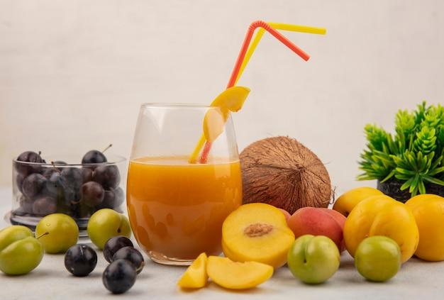 Вид сбоку на здоровые свежие и красочные фрукты, такие как терн, на стеклянной миске, кокосовый орех со свежим персиковым соком на стакане на белом фоне
