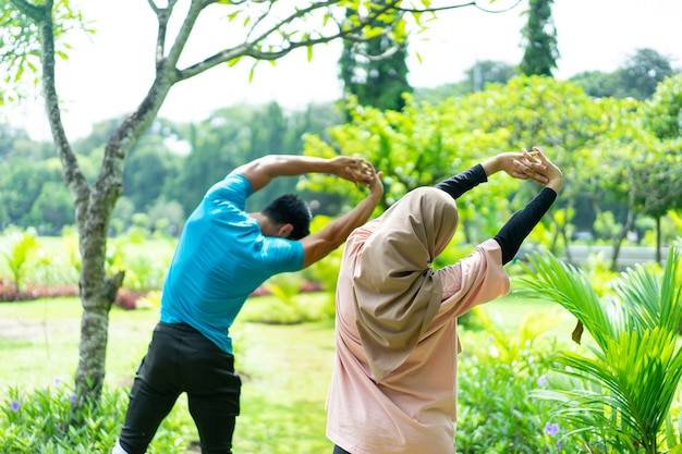 公園でアウトドアスポーツをするときに一緒に腕の運動をしているヒジャーブの女の子と筋肉質の男性の側面図