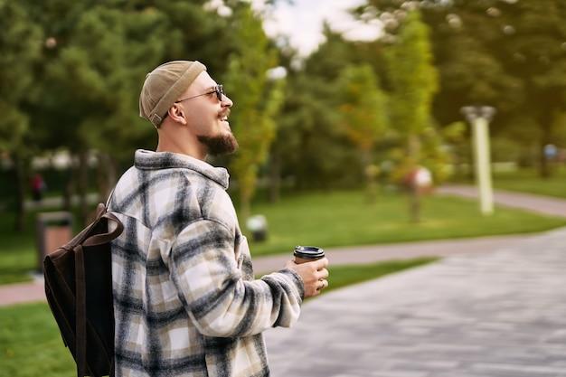 힙스터 수염 난 학생의 옆모습은 도시 공원 휴식일에 걷는 동안 옆으로 보인다