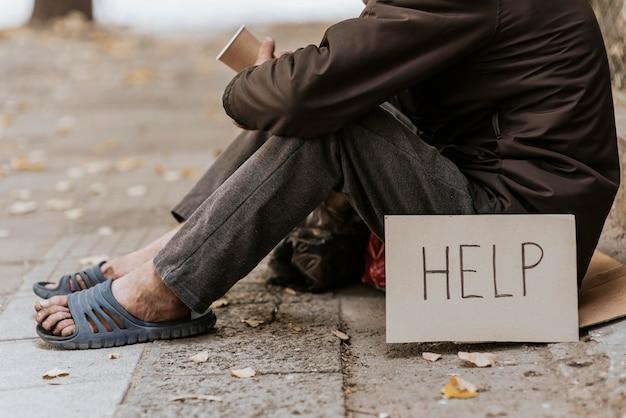 Бездомный на улице, вид сбоку с чашкой и знаком помощи