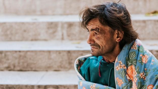 Бездомный мужчина на открытом воздухе с одеялом рядом с лестницей, вид сбоку